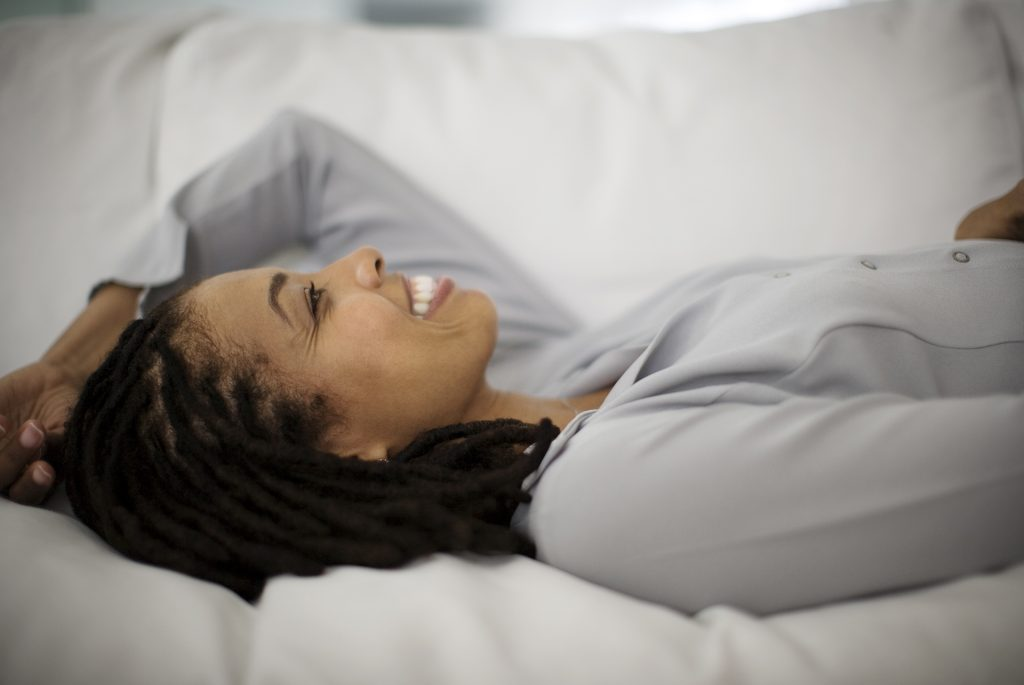 smiling woman with locs laying down on couch