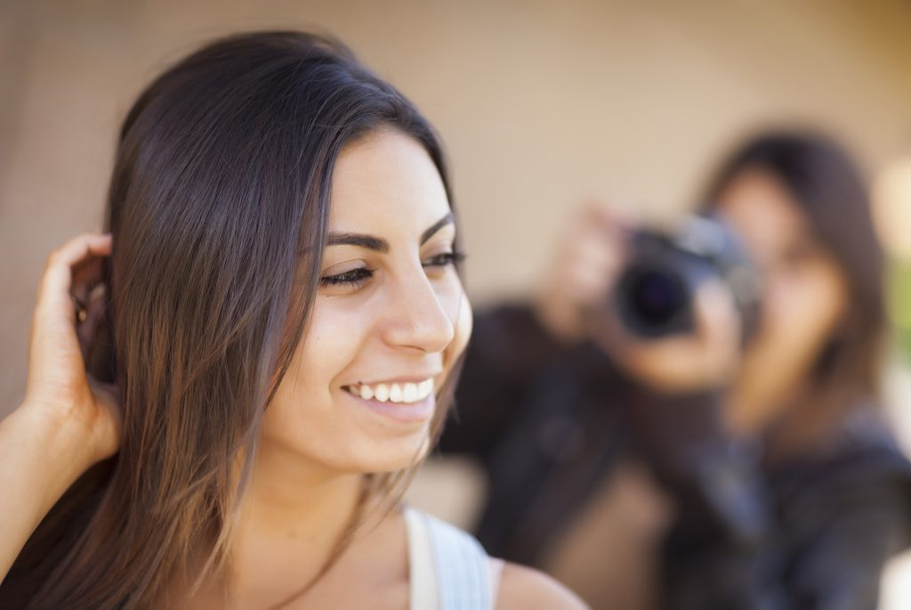 Attractive Young Adult Mixed Race Female Model Poses for a Photographer Outside.